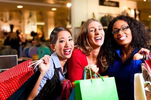 Друзья по магазинам с сумками в торговом центре