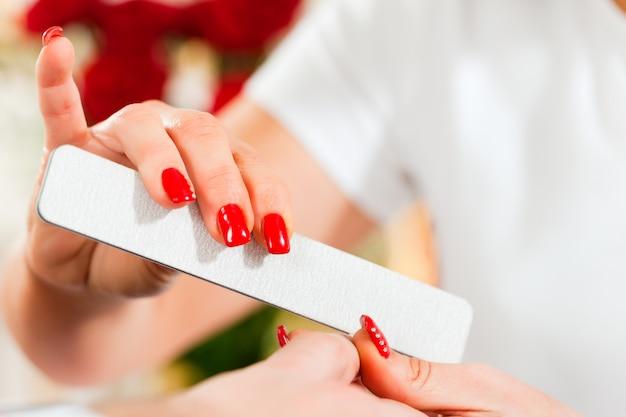 Женщина в маникюрном салоне получает маникюр