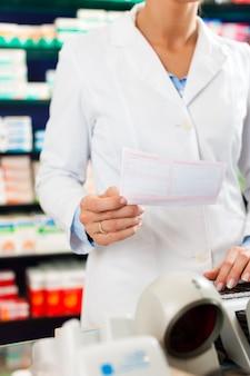 Женский фармацевт на кассе в аптеке