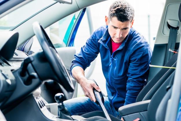 若い男が車の内部を掃除するための真空を使用して