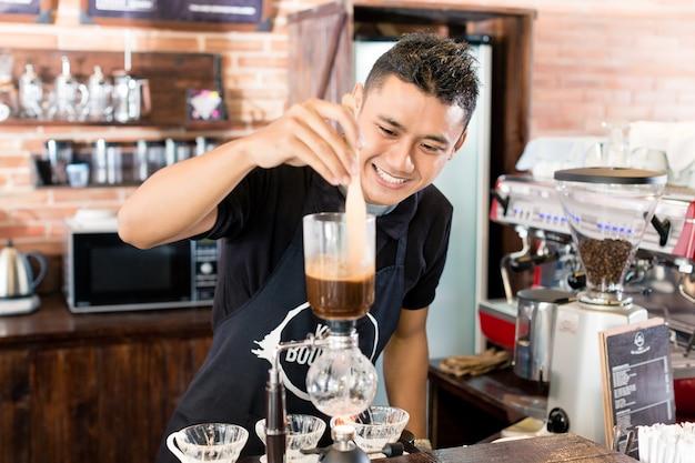 アジアのコーヒーショップでドリップコーヒーを準備するバリスタ