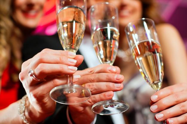 バーでシャンパンを持つ人々