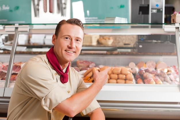 Мясник, указывающий на свежее мясо для продажи