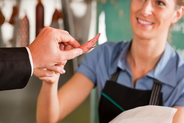 Мясник дает нарезанный кусок мяса клиенту