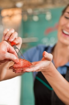 Мясник женского пола, продающий свежее мясо клиенту