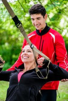 スリングトレーニングでトレーナーとスポーツの女性