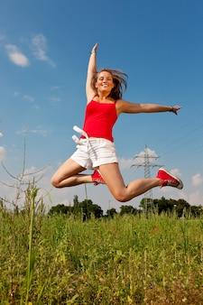 電柱の前でジャンプ女性