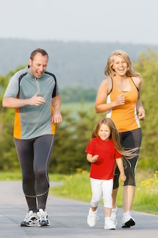 屋外スポーツのために実行している家族