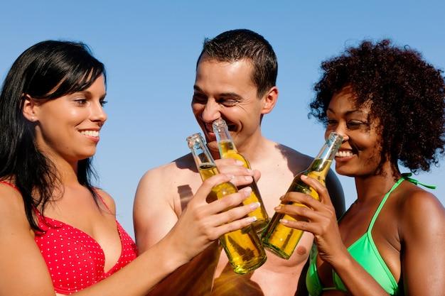 水着でビールを飲む友人のグループ