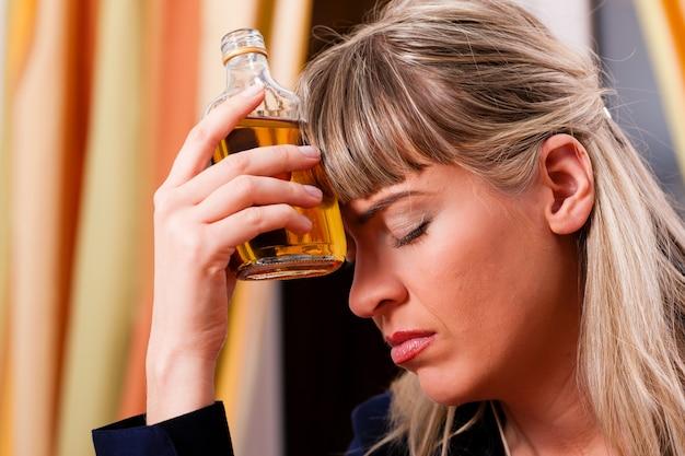 アルコール乱用-ブランデーを飲みすぎている女性