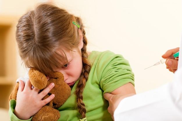 子供に注射器を適用する小児科医