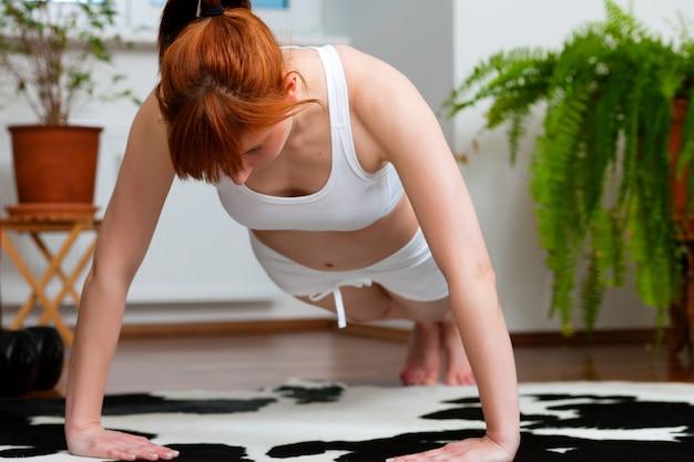 女性は自宅で運動しています
