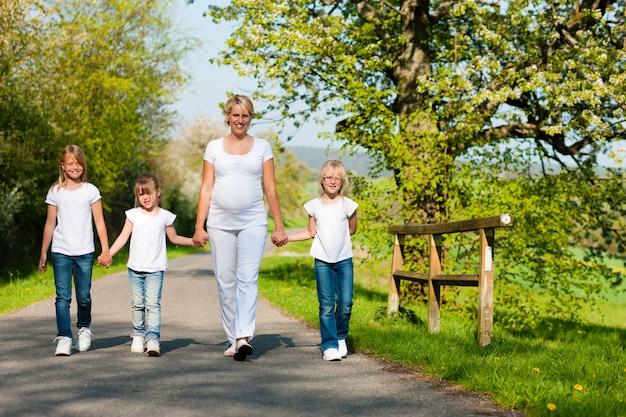 Семья - дети и мама идут по тропинке