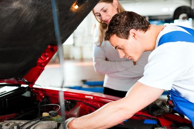 Женщина разговаривает с автомехаником в ремонтной мастерской