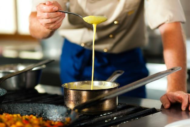 レストランまたはホテルのキッチンで料理をするシェフ