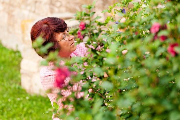 彼女の庭の花を持つ女性