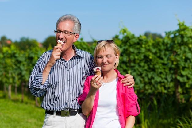 Пожилые супружеские пары, имеющие прогулку с мороженым
