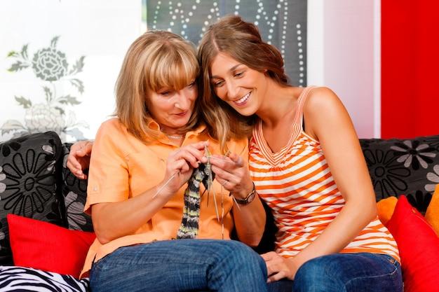 彼女の娘の編み物を教える女性