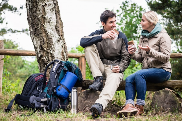 ツリーの下で休憩を取ってハイキングをカップルします。