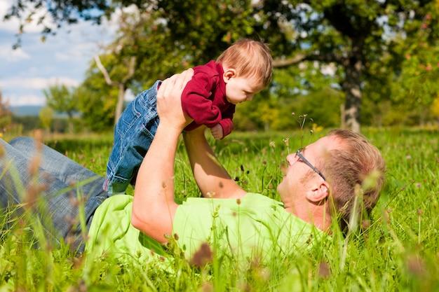 牧草地で赤ちゃんと遊ぶ父