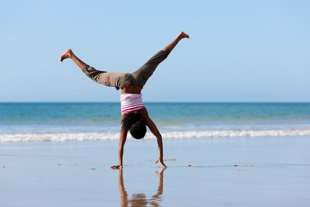 ビーチで体操をしている陽気な女性