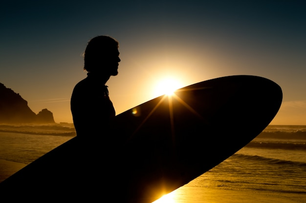 Серфер и доска в вечернем солнце
