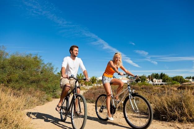 ビーチでのサイクリングの休日のカップル