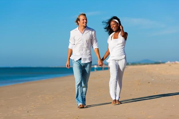 幸せなカップルが歩いてビーチで実行