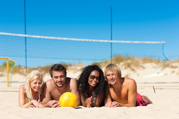 Друзья играют в пляжный волейбол