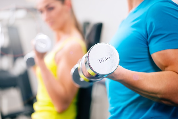 Тренировка пары для фитнеса в спортзале с весами