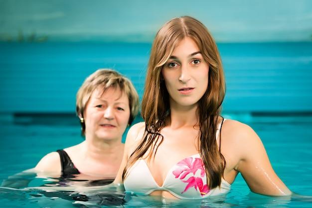 スイミングプールで成熟した若い女性
