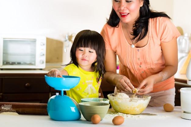 アジアの母と娘の自宅の台所で