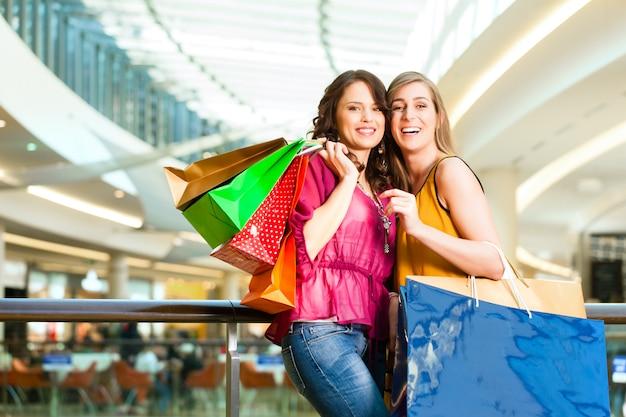 Женщины с покупками в торговом центре