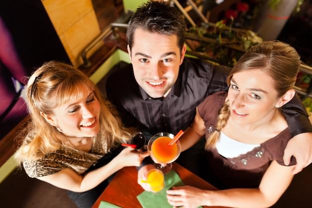 Молодые люди пьют коктейли в баре или ресторане