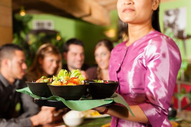 Молодые люди с официанткой едят в тайском ресторане