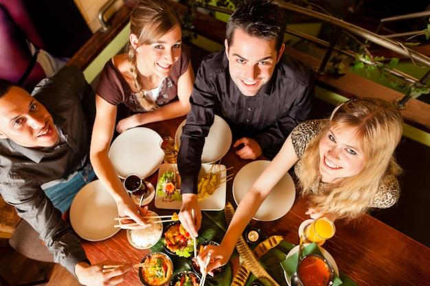 タイのレストランで食べる若者