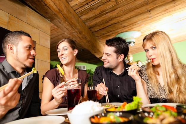 Молодые люди едят в тайском ресторане