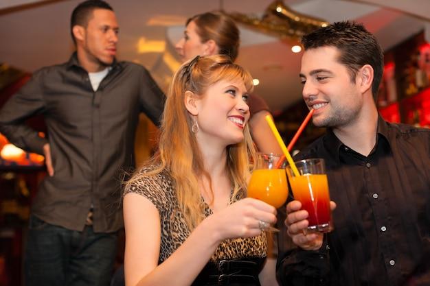 若いカップルのバーやレストランでカクテルを飲む