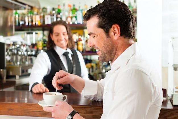 Бариста с клиентом в его кафе или кафе