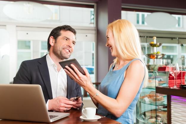 Мужчина и женщина сидят в кафе