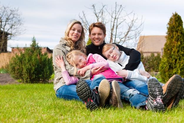春の牧草地に一緒に座っている家族