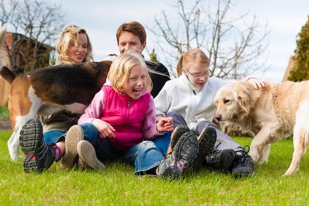 犬と一緒に牧草地に座っている家族