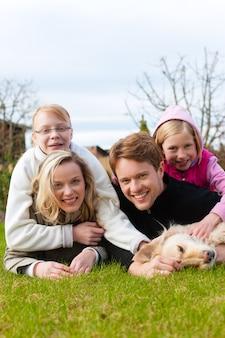 家族は牧草地に一緒に座っています。