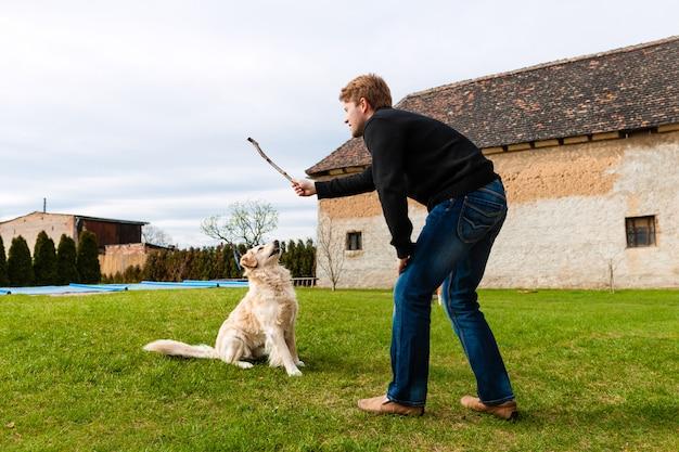 Молодой человек играет со своей собакой в саду