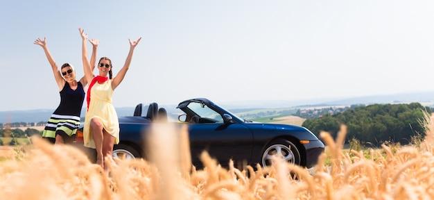 コンバーチブル車で休憩を持っている女性