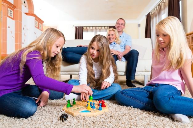 Семья играет в настольную игру дома