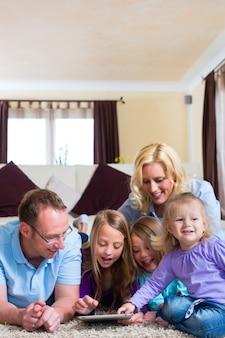 Семья играет с планшетного компьютера на дому