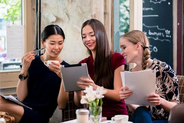 コーヒーショップでファイルを保持している若い女性