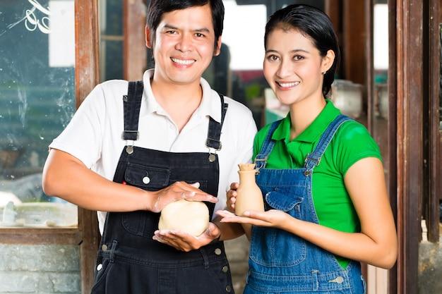 粘土スタジオで手作りの陶器を持つアジア人