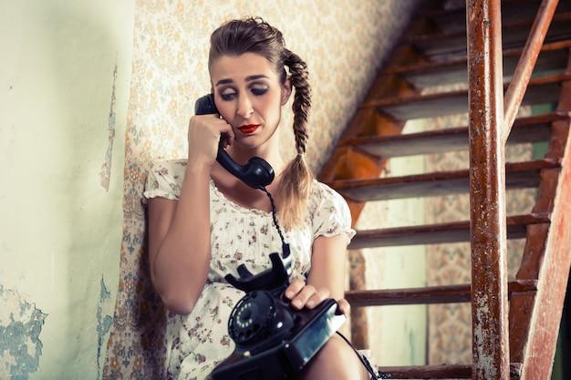 階段に座って電話で泣いている女性